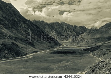 Aerial view of moody and rocky landscape of Kargil, with mountain peaks and cloudy sky  in background , green valley , Leh, Ladakh, Jammu and Kashmir, India. Tinted image. - stock photo