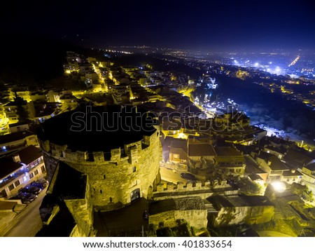 Aerial view of old Byzantine castle and the city of Thessaloniki at night, Greece. Image taken with action drone camera causing distortion and blur. - stock photo