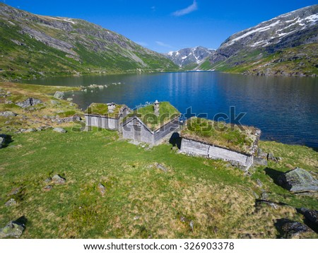 Aerial view of old norwegian huts by picturesque lake surrounded by mountains in Gaularfjellet mountain pass in Norway - stock photo