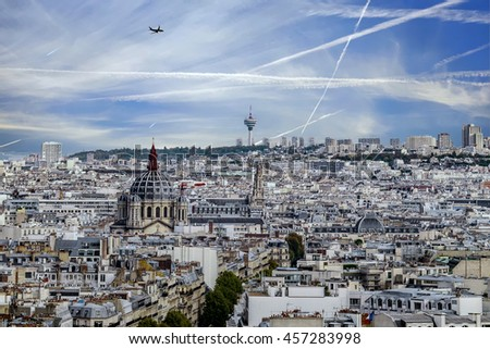 Aerial view of Paris, France. Blue sky, buildings and plane trails in the sky with plane. Shot in october daylight.