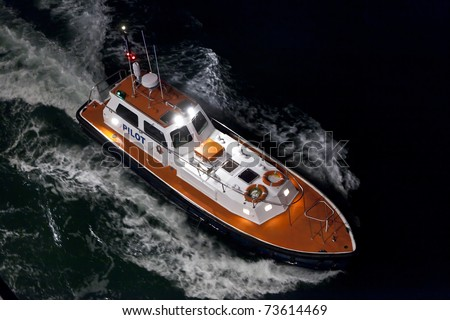 aerial view of pilot boat motoring through dark seas at night.