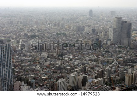 Aerial view of polluted modern city wrapped in smog - stock photo