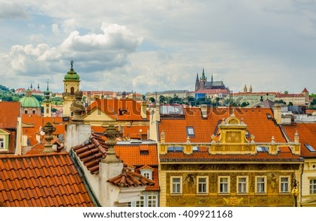 aerial view of prague castle hidden behind red-tile rooftops. - stock photo
