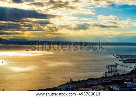 Aerial view of Puget Sound at Seattle lit up by sun rays, with Olympic Mountains in the distance