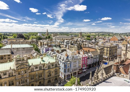 Aerial view of roofs and spires of Oxford, England with blue sky in background - stock photo
