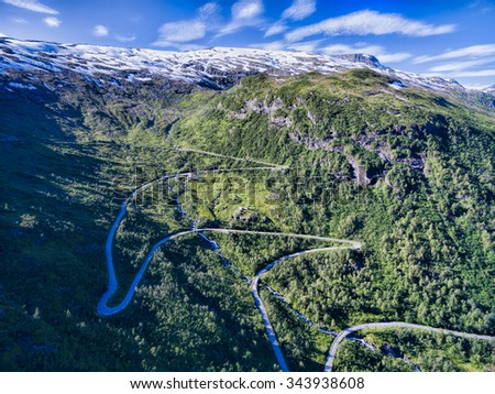 Aerial view of serpentine mountain road in Gaularfjellet mountain pass in Norway surrounded by snowy mountain peaks - stock photo