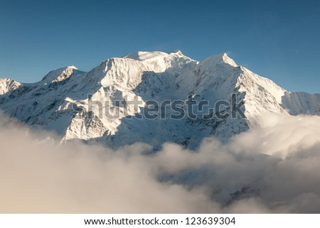 Aerial view of snow covered Mont Blanc peak in winter from the French side of the alps on a clear, blue, cold and sunny winter day. / Mont Blanc in Winter - stock photo