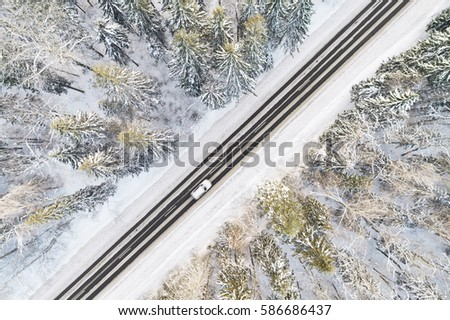 Aerial view of snow covered road in winter forest, car passing by, motion blur