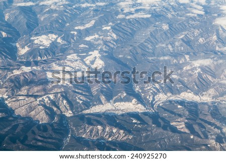 Aerial view of snowy mountain tops with white clouds  - stock photo