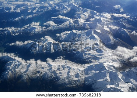 Aerial view of snowy mountains and clouds, opposite the sunlight