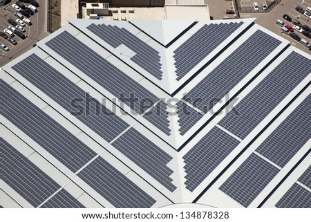 Aerial view of solar panels cover a portion of a very large building - stock photo
