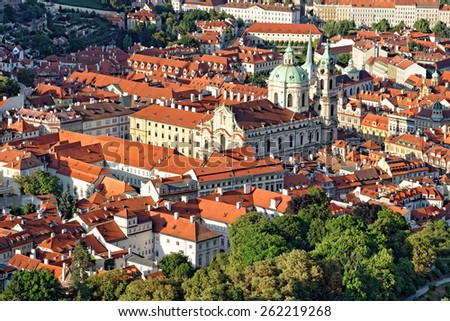 Aerial view of St. Nicholas church in the Lesser town district and the red roofs of  Prague, Czech Republic. - stock photo