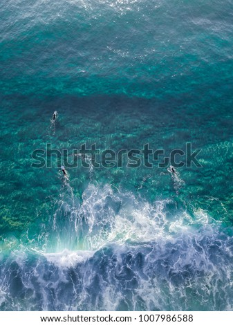 Aerial view of surfer in the turquoise water.