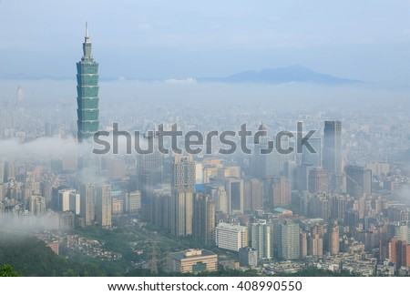 Aerial view of Taipei, the capital city of Taiwan, on a foggy spring morning with prominent Taipei 101 Tower above the clouds among skyscrapers in downtown & Datun Mountain in the distant background - stock photo