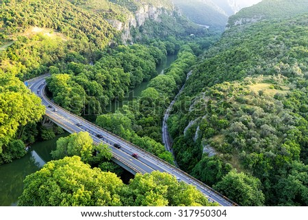 Aerial view of the bridge and the road over the river Pinios in the green valley of Tempe in Greece - stock photo