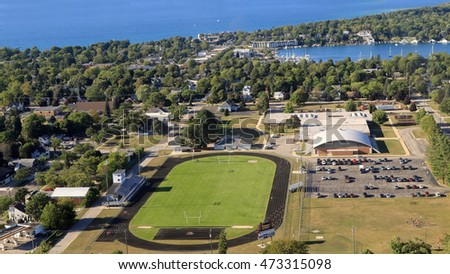 Aerial view of the campus of Charlevoix high school, with track and stadium and surrounding neighborhood, in Northern Michigan.