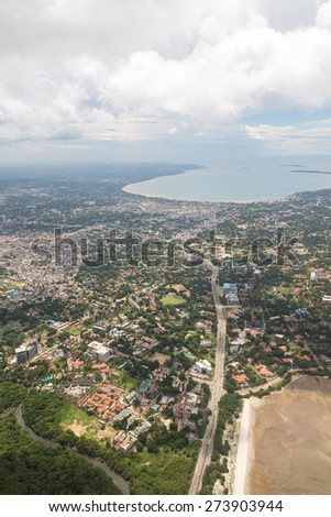 Aerial view of the city of Dar Es Salaam along the shores of the Indian Ocean showing the densely packed buildings - stock photo