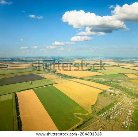 Aerial view of the countryside with village and fields of crops in summer.