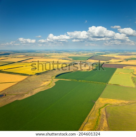 Aerial view of the countryside with village and fields of crops in summer. - stock photo
