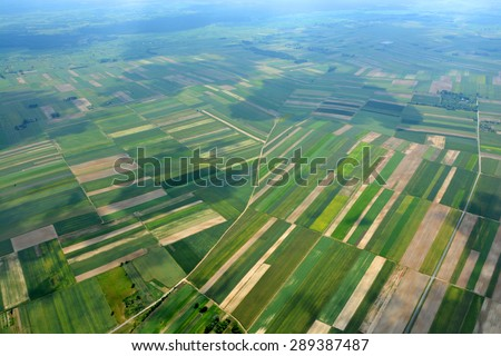 Aerial view of the countryside with village and fields of crops in summer