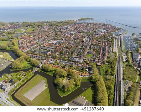 Aerial view of the Dutch city Enkhuizen in The Netherlands with lake IJsselmeer and a clear horizon with blue sky.  - stock photo