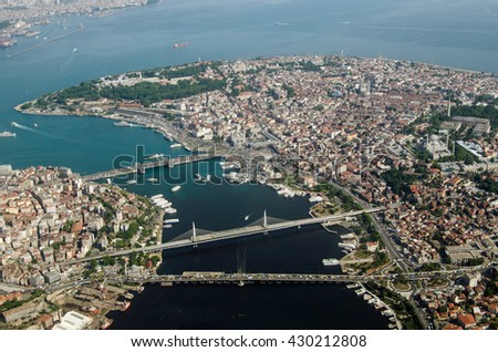 Aerial view of the Golden Horn and Old City of Istanbul with the famous Topkapi Palace, Hagia Sophia and Blue Mosque visible in the distance and the bridges crossing the city's natural harbour. - stock photo