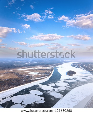 Aerial view of the great river with floating ice floes during the spring day. Drifting of ice. Driving of ice. Ice floe. - stock photo