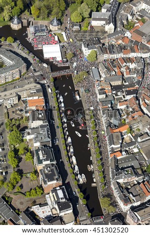 Aerial view of the harbor of Breda, Holland with a lot of boats in the water and many people in the streets.