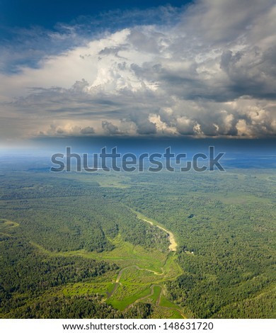 Aerial view of the house hunter on the forest plain which is under the rain clouds in summer. - stock photo