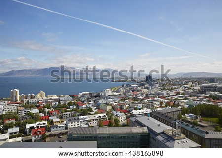 Aerial view of the North of Reykjavik, the capital of Iceland under steely blue skies with airplane smoke  trails - stock photo