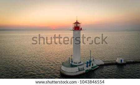 Aerial view of the Odessa Lighthouse in Ukraine as the sun rises behind it.