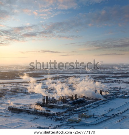 Aerial view of the oil refinery with smoking chimneys in winter against sunset. West Siberia. - stock photo