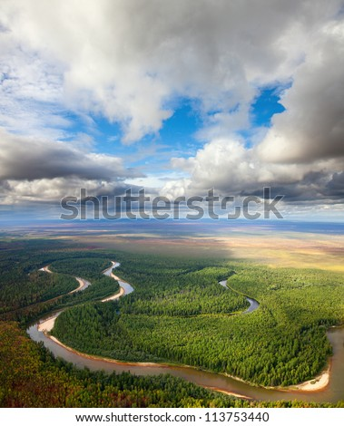 Aerial view of the river executing the loop during the cloudy day of autumn. - stock photo