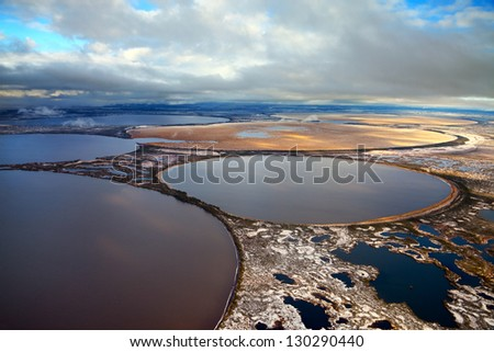 Aerial view of the some round lakes on marshy terrain in the cold autumn day. The two lakes were overgrown marsh grass. - stock photo