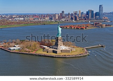Aerial view of the Statue of Liberty in New York City, USA with Downtown Brooklyn and Governors island in the background. The statue is an icon of freedom and of the United States - stock photo
