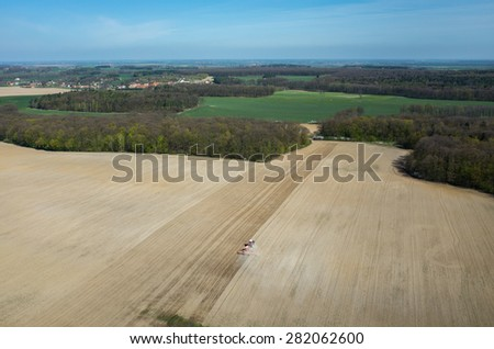 Aerial view of the the tractor harrowing the large brown field in spring season - stock photo