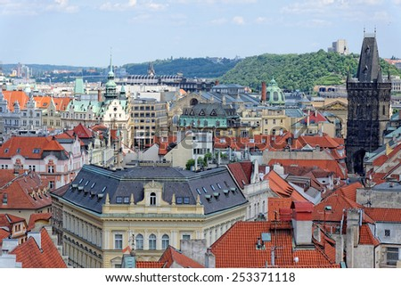 Aerial view of the traditional red roofs of the city of Prague, Czech Republic with the Powder tower and Vitkov Hill in the distance.