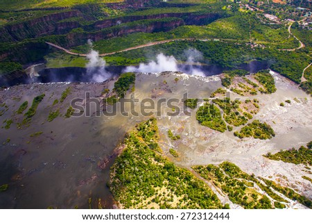 Aerial view of the Zambezi river right before Victoria Falls.  Clouds and mist rising up from the falls. - stock photo