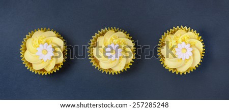 Aerial view of three lemon cupcakes with fondant flower in single file on a blue slate  background.