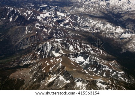Aerial view of Top of sierra nevada mountains during the summer with a small amount of snow still left on the mountains.                                - stock photo