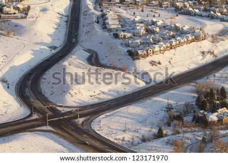 Aerial view of traffic intersection and houses in the snow. - stock photo