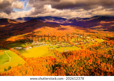 Aerial view of Trapp Family Lodge during peak foliage season with Mt. Mansfiled in the background, Stowe, Vermont, USA - stock photo