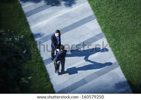 Aerial view of two businessmen shaking hands on sidewalk - stock photo
