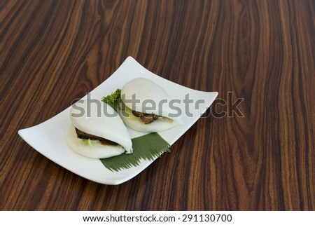 Aerial view of two Chinese steamed buns sandwich of barbecue marinated pork. - stock photo