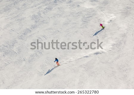 Aerial view of two skiers on a steep, black ski run with trails of snow dust behind them. - stock photo