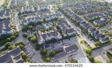Aerial view of typical multi-level apartment building with swimming pool, surrounded by green garden and rows of cars in parking lots in Houston, Texas, US. Residential recreation concept. Warm light.