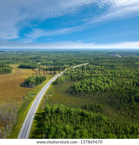 Aerial view of unlimited space of forest plain and cars which are riding on highway. - stock photo