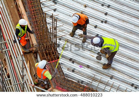 Aerial view of unrecognized civil engineer supervise roof construction workers work in a construction site. Building development concept with copy space