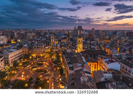 Aerial view of Valencia, Spain at sunset. Illuminated Plaza de la Reina with many cafes and restaurants and very popular among tourists. Cloudy colorful sky - stock photo