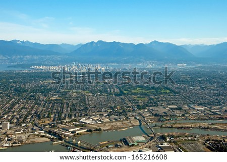 Aerial view of Vancouver downtown city in British Columbia with beautiful mountains in background - stock photo